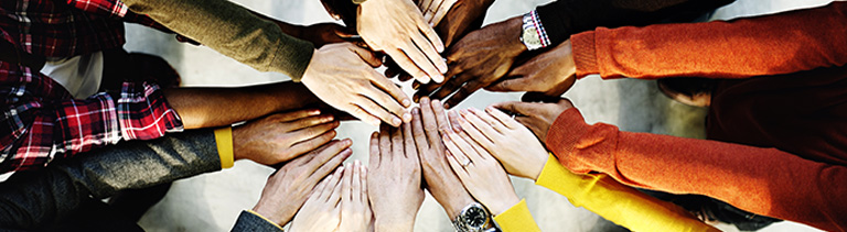 diverse hands joining in middle